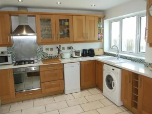 A large wooden kitchen, with modern white worktops and a large window letting in lots of light.