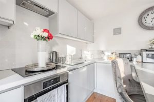 Modern, white kitchen with a vase of flowers on the worktop